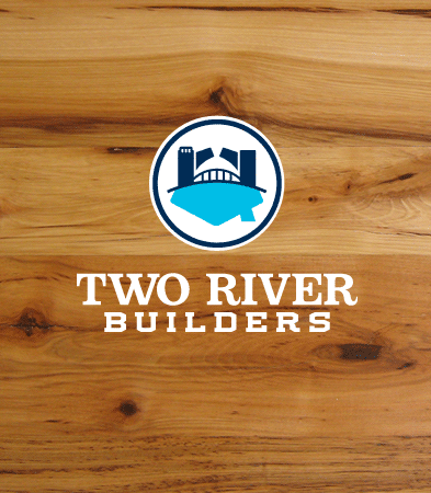 Two River Builders logo on a wood background